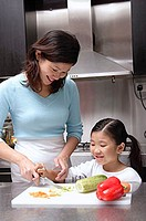 Mother cutting vegetables, daughter helping her