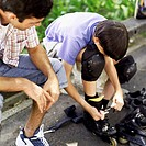 Teenage boy sitting on a park bench with his father fastening on roller blades