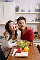 Couple side by side in kitchen, smiling at camera