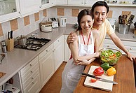 Couple in kitchen, smiling at camera, portrait