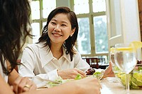 Woman in restaurant smiling at person next to her