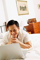 Man in bedroom, looking at laptop, hands clasped, under chin