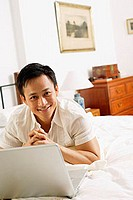 Man in bedroom, using laptop, hands clasped, looking at camera