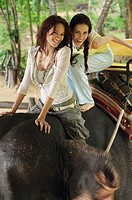Two young women riding on elephant, Phuket, Thailand