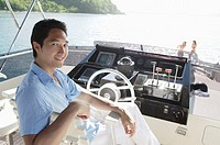 Man sitting at helm of yacht, looking at camera