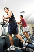 Men using cross trainer in gym, low angle view