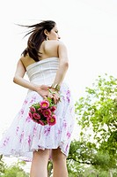 Woman holding bouquet of flowers behind her back (thumbnail)