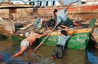 Harbour workers trying to release a boat run aground. Mandalay, Burma