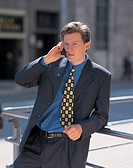 portrait of a businessman leaning on a railing talking on a mobile phone