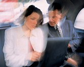 blurred shot of a business executives sitting in car and working on a laptop