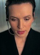 close-up of a woman wearing a telephone headset and looking down