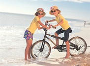 two sister on the beach with a bicycle