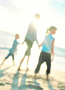 family holding hands walking on beach (blurred)