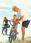 grandfather teaching granddaughter to ride bicycle on the beach