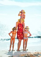 mother standing with three young daughters (4-8) on the beach