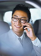 portrait of a young man talking on a mobile phone in car