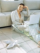 portrait of a businesswoman sitting on the floor in front of a laptop