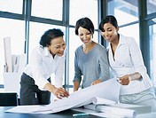 three businesswomen looking at a blueprint in an office