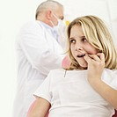 Young woman holding lip at dentists office