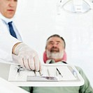 A dentist choosing his tools before examining his patient
