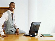 businessman sitting on a desk wearing a hands free