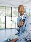 businessman holding a mobile phone and a laptop in an office