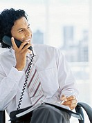 businessman talking on a landline phone in an office