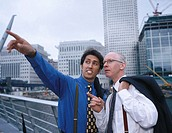 Young businessman pointing ahead with an elderly businessman standing beside him