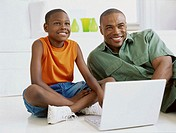 father and his son in front of a laptop