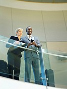 businessman and businesswoman standing at an airport lounge