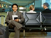 portrait of a businessman sitting on a bench at an airport
