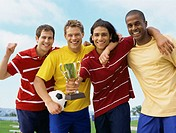 portrait of four young men holding a trophy and a soccer ball