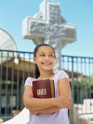 close-up of a girl holding the bible in front of a cross