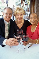 portrait of a mature couple and a mid adult woman making a toast in a restaurant