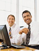 two businessmen sitting in front of a computer