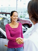 young woman shaking hands with a car dealer in a car showroom