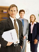portrait of a businessman carrying a resume with two business executives behind him