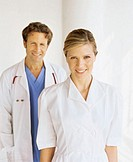 portrait of a female nurse smiling and a male doctor standing behind her