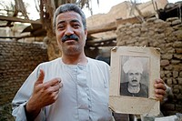 Barnabe, head of a coptic family, showing his late father photo. He was the founder of an important weaving workshop. Country life in small villages a...