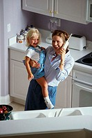 High angle view of a mother carrying her daughter and talking on a cordless phone