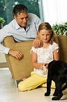 Mid adult man and his daughter playing with their dog