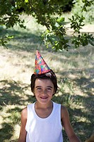 Portrait of a boy wearing a birthday hat and smiling