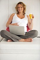 Portrait of a pregnant woman sitting on a couch with a laptop on her lap and holding a glass of juice