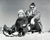 Close-up of a mother with her two children sitting on a sled