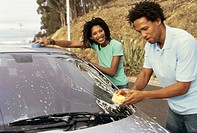 Close up of a young couple washing a car