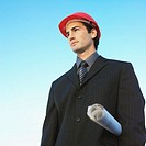 Businessman wearing a hard hat, carrying site plans