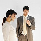 Businesswoman using headset with businessman in background using mobile phone