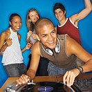 Male dj playing the decks with three people dancing behind him
