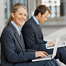Businessman and businesswoman sitting on a pavement both using laptops