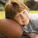portrait of a boy resting his head on a football